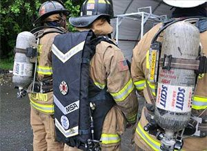 Photo Mark E. Brady A firefighter wearing the SCBA prototype is seen alongside old models. View slideshow from testing