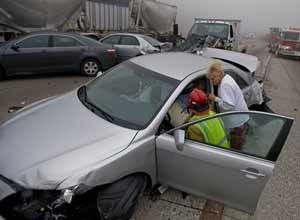 AP Photo/Eric ReedRegistered Nurse Stacy Blevins and EMSpersonnel attend to injured passengers after a multi-vehicle collision in the heavy fog at the Cajon Pass on Interstate 15 near Oak Hills, Calif., on Wednesday.