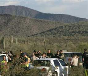 Law enforcement officers from different agencies gather to coordinate the search for a suspect that shot a Pinal County Sheriff's deputy Friday April 30, 2010 in the desert southwest of Stanfield, Ariz. (AP Photo)