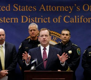 McGregor Scott, the United States Attorney for the Eastern District of California, discusses the arrests of 31 people he said are connected to a violent, drug-running multi-state street gang, during a news conference Wednesday, Feb. 14, 2018, in Sacramento, Calif. (AP Photo/Rich Pedroncelli)