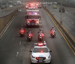 Police and fire department vehicles lead a procession along Franklin D. Roosevelt East River Drive with the unidentified remains of victims of the Sept. 11, 2001 attacks as they are returned to the World Trade Center site. (AP Photo/Julio Cortez)