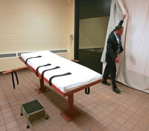 In this Nov. 2005 file photo, Larry Greene, public information director of the Southern Ohio Correctional Facility, demonstrates how a curtain is pulled between the death chamber and witness room at the prison in Lucasville, Ohio. (AP Photo/Kiichiro Sato, File)