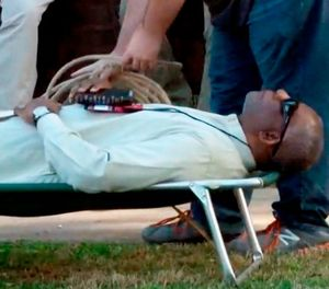 In this April 17, 2018, file image from video provided by KTHV-TV, a death penalty protester outside the Arkansas governor's mansion in Little Rock prepares to tie rope around Pulaski County Circuit Judge Wendell Griffen who is laying on a cot in protest of executions. (KTHV/TEGNA Inc. via AP, File)