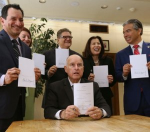 Gov. Jerry Brown (seated) signed the bill Tuesday. (AP Photo/Rich Pedroncelli)