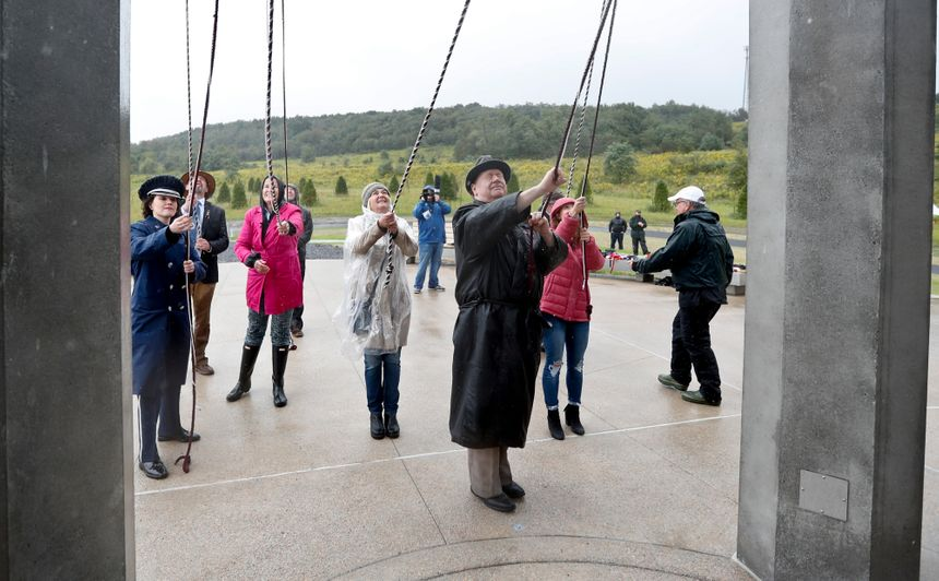 Members of passenger families, friends and volunteer repesentatives pull the ropes to ring the chimes at the dedication of the 93-foot tall Tower of Voices on Sunday, Sept. 9, 2018 at the Flight 93 National Memorial in Shanksville, Pa. The tower contains 40 wind chimes representing the 40 people that perished in the crash of Flight 93 in the terrorist attacks of Sept. 11, 2001.(AP Photo/Keith Srakocic, Pool)