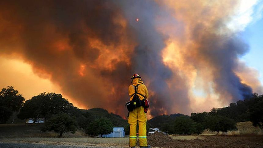 A firefighter runs while trying to save a home as a wildfire tears through Lakeport, Calif. (Photo/AP)