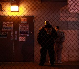 A U.S. Immigration and Customs Enforcement (ICE) officer stands next to a fugitive before entering a staging facility in Los Angeles, Wednesday, Dec. 9, 2009. (AP Photo/Jae C. Hong)