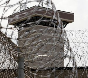 This Tuesday, July 3, 2012 photo shows coils of razor wire and a guard tower at the maximum-security Mount Olive Correctional Center in Mount Olive, W.Va. (AP Photo/Steve Helber)