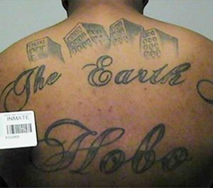"""This undated photo in a court filing provided by the United States Attorney's office in Chicago, shows Paris Poe's back tattoo that reads """"The Earth Is Our Turf"""", and Hobo. (United States Attorney's office in Chicago via AP)"""