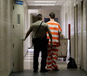 In this Feb. 21, 2013, file photo, an inmate at the Madera County, Calif., Jail is taken to an inmate housing unit in Madera, Calif. (AP Photo/Rich Pedroncelli, File)