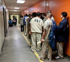 In this Sept. 29, 2011 file photo, inmates at the Cook County Jail in Chicago, line up to be processed for release. (AP Photo/M. Spencer Green File)