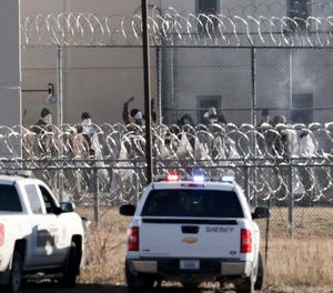 Prisoners burn objects as they mill in a courtyard behind razor wire at the Tecumseh State Correctional Institution in Tecumseh, Neb., Thursday, March 2, 2017. (AP Photo/Nati Harnik)