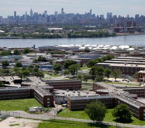 In a June 20, 2014, file photo, the Rikers Island jail complex stands in New York with the Manhattan skyline in the background. (AP Photo/Seth Wenig, File)