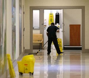 In this photo taken June 21, 2017, a detainee mops a floor in a hallway of the Northwest Detention Center in Tacoma, Wash., during a media tour of the facility. (AP Photo/Ted S. Warren)