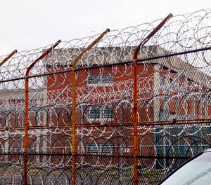 In this March 16, 2011, file photo, a security fence surrounds the inmate housing on New York's Rikers Island correctional facility in New York. (AP Photo/Bebeto Matthews, File)