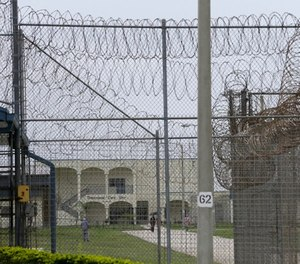 A prisoner works on the lawn at the Dade Correctional Institution on Thursday, July 10, 2014, in Florida City, Fla.