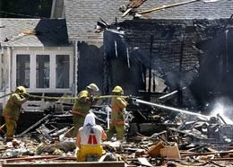 Firefighters work at a destroyed home after a natural gas explosion in Carlinville, Ill., in August last year when two people died. (AP Photo/Seth Perlman)
