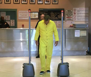 State correctional department spokesman Gerard Shields, wearing a yellow prison jumpsuit, and walks through the Cellsense detector at a demonstration Wednesday.