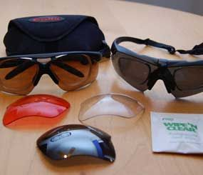 On the left, Bollé Vigilante glasses with their hard case and three extra pop-in lenses. On the right, ESS ICE eyeshields and an eyeglass cleaning packet. Both sunglasses are shown with prescription inserts mounted. (PoliceOne Image)
