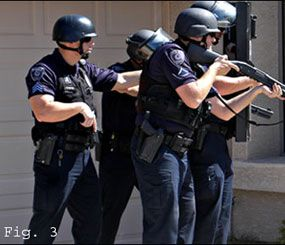 The sergeant supervising this arrest team uses the safety circle to control his muzzle while still directing the team of officers.  The officers in front of him are in a solid ready position.