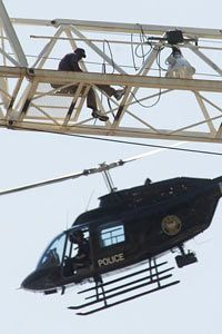 A homicide suspect identified as Carl Roland is buzzed by a law enforcement helicopter atop an 18-story construction crane in the Buckhead area of Atlanta in May of 2005. (AP Photo/John Amis)