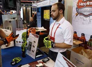 "Photo Rick MarkleyHexArmor's new rescue gloves sell ""like crazy"" for $35 and $45 at FDIC 2012, according to Patrick Beadling, the company's marketing manager. Marketing Specialist Adam Dietsch (pictured) shows the gloves to a potential customer."