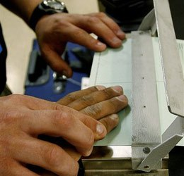 U.S. Immigration and Customs Enforcement (ICE) agent finger prints an alien during an operation Friday, July 14, 2006 in Oklahoma City. (AP photo)