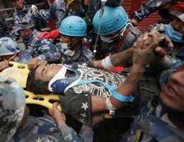 A teen is carried on a stretcher after being rescued by Nepalese policemen and U.S. rescue workers from a building that collapsed during the Nepal 2015 earthquake. (AP Photo/Niranjan Shresta)