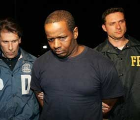 James Cromitie, center, is escorted by an NYPD officer and an FBI agent after being arrested for plotting to bomb New York synagogues and shoot down military aircraft. (AP Photo)