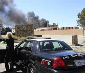 """A Redwood City (Calif.) police officer watches as smoke billows from a fire in May 2011. Now that the department has deployed Nixle, city officials wishing to issue a """"shelter in place"""" order for an affected area such as this one can do it simultaneously via text, email, and online. (AP Photo File Photo)"""