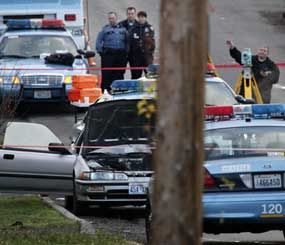 Police work at the scene where a man suspected of gunning down four police officers was shot and killed by a lone Seattle patrol officer who came across the stolen car in a south Seattle neighborhood about 2:45 a.m. (AP Photo)