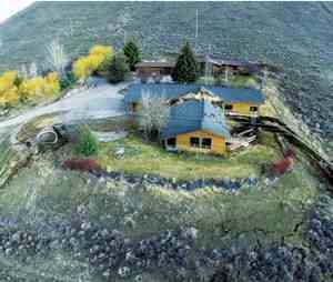 This aerial image provided by Tributary Environmental shows a home damaged by a landslide Friday, April 18, in Jackson, Wyo. A slow-moving landslide in Jackson sped up significantly Friday, splitting this house in two, causing a huge uplift in a road and a Walgreens parking lot, and threatening to destroy several other unoccupied homes and businesses. (AP Photo/Tributary Environmental)