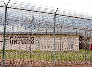 This April 22, 2009, file photo, shows a prisoner, far right, seen behind layers of wire razor fencing at the Louisiana State Penitentiary at Angola, La. (AP Photo/Judi Bottoni, File)