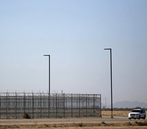 In this Jan. 20, 2016 file photo, an unmarked police truck patrols the outside of a private detention center operated by CoreCivic in Eloy, Ariz. (AP Photo/Ricardo Arduengo, File)