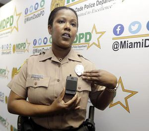 Miami-Dade Police Department PIO Marjorie Eloi shows how to turn on and off a body camera, which 1,000 officers will begin using over the next few months, during a news conference, Thursday, April 28, 2016. (AP Image)