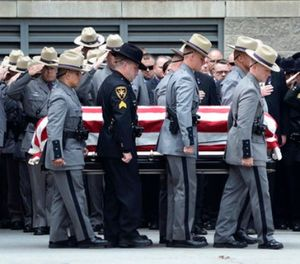 The casket of slain New York state trooper, Joel Davis, is carried out of the Magrath Sports Complex at Fort Drum, N.Y., by law enforcement personnel, during Davis's funeral service, Saturday, July 15, 2017. (AP Photo/Heather Ainsworth)