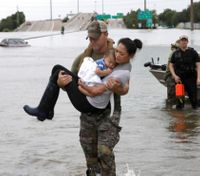 Photo of cop carrying woman, baby through Harvey floodwaters goes viral