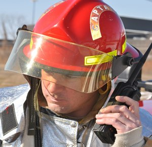 Mike Fortmann of the 128th Air Refueling Wing Fire Department, Milwaukee, communicates with headquarters via a handheld radio during a training exercise. (Image Wisconsin Air National Guard Staff Sgt. Jeremy Wilson)