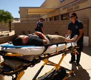 EMS cots aren't designed to be lifted or carried. They're designed to securely transport a patient from point A to point B, with attendants guiding their movement – and not at a fully-extended loading height, either. (Photo/DoD)