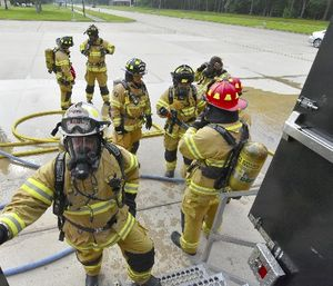 Arnold Air Force Base paramedic/firefighters prepare to enter the Kentucky Fire Commission mobile live fire rescue simulation training structure on May 11. Forty-one base firefighters, participated in the annual training experiencing high temperatures and smoke, and practicing firefighting and self-rescue techniques. (U.S. Air Force photo/Rick Goodfriend)