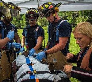 Firefighters and paramedics work together to secure a patient during an aircraft mishap exercise. (Photo/U.S. Air force by Staff Sgt. Areca T. Bell)