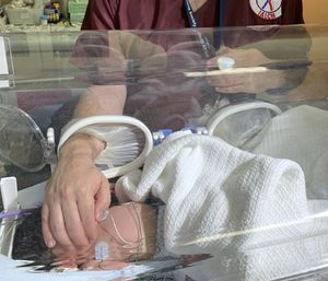 A baby is treated at a hospital after being rescued from a storm drain. (Photo/AP)
