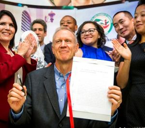 Illinois Gov. Bruce Rauner smiles while surrounded by law enforcement officials and immigrant rights activists in Chicago's Pilsen neighborhood Monday, Aug. 28, 2017, after signing legislation that will limit how local and state police can cooperate with federal immigration authorities. (Ashlee Rezin/Chicago Sun-Times via AP)
