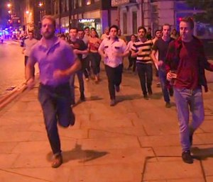 In this image taken from video footage, people run from the scene of attack, alongside a man strolling holding a pint of beer, right, in London, late Saturday, June 3, 2017. (Sky news via AP)