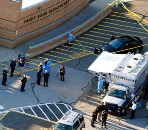 In this Dec. 14, 2012, file photo, officials stand outside of Sandy Hook Elementary School after a shooting in Newtown, Conn.  (AP Photo/Julio Cortez, File)