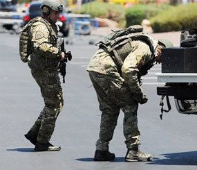 Las Vegas police officers prepare to go near the scene of a shooting in Las Vegas, Sunday. (AP Image)