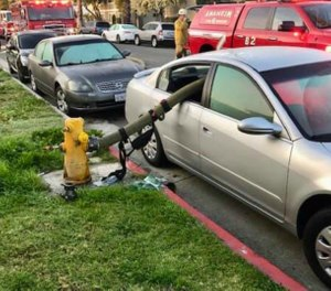 Firefighters broke both back passenger windows of the parked car and snaked the hose through, and eight people were eventually evacuated from the house fire. (Photo/Anaheim Fire & Rescue)