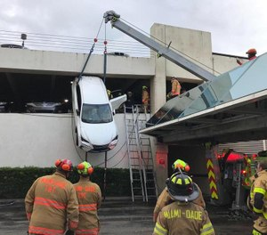 Miami-Dade Fire rescue crews jumped into action Thursday to rescue a driver from an SUV that was left dangling from a Miami Springs parking garage. (Photo/Miami Dade Rescue)