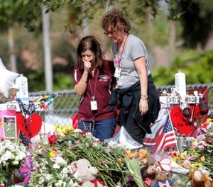 Margarita Lasalle, a bookkeeper and Joellen Berman, a guidance data specialist, look at a memorial Friday, Feb. 23, 2018 as teachers and school administrators returned to Marjory Stoneman Douglas High School for the first time since 17 victims were killed in a mass shooting at the school, in Parkland, Fla. (Mike Stocker/South Florida Sun-Sentinel via AP)