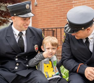 Canton Firefighter/ Paramedic Benjamin Lasure (left) was honored for saving 7-year-old Colton Grewell (middle) from a house fire on May 6. (Photo/Canton City Fire Department)
